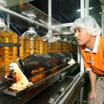 A worker inspects bottles of palm cooking oil along a production line at Yee Lee Corp.'s Yee Lee Edible Oils factory, in Ipoh, Perak, Malaysia, on Saturday, May 3, 2008. Yee Lee Edible Oils exports 20% of the 15,000 tons of cooking oil produced per month at this facility. Photographer: Goh Seng Chong/Bloomberg News